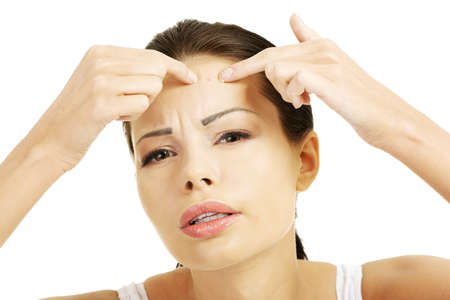 tratamientos corporales: Mujer joven con la espinilla en la cara. Tratando de exprimir. Aislado sobre fondo blanco.