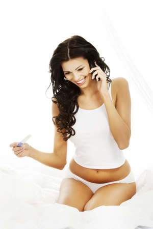 Happy beautiful woman on bed with pregnancy test in hand calling to somebody photo