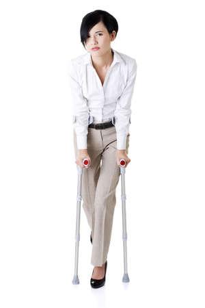 Junge Geschäftsfrau mit Krücken, isoliert auf weiß. Behindertenzugang in Arbeit.