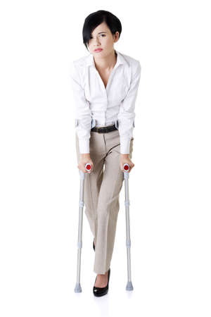 crutches: Young businesswoman with crutches, isolated on white. Disabled person in work.  Stock Photo