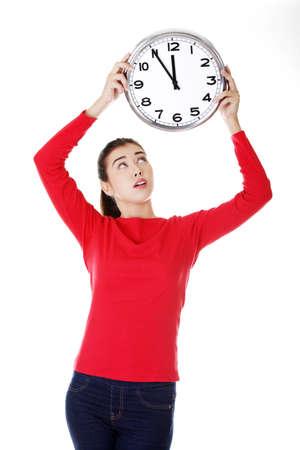 Shocked woman holding office clock, isolated on white bacvkground  photo
