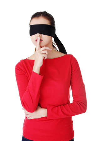 Blindfold woman with finger on lips. Gesturing for quiet and keeping secret