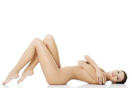 mujer sexi desnuda: Sexy mujer desnuda en forma con la piel limpia y sana acostado, aislado en blanco Foto de archivo