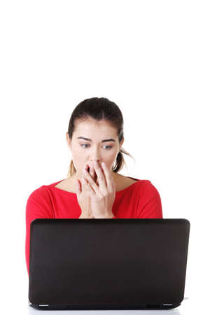 disgusted: Surprised and disgusted woman working on laptop. Isolated on white.  Stock Photo