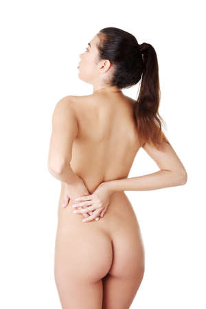 anatomy naked woman: Young woman with pain in her back. Isolated