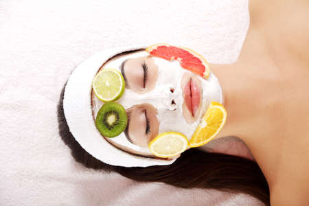 Attractive young woman with fruit mask on a face at spa saloon 版權商用圖片