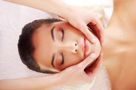 Beautiful young relaxed woman enjoy receiving face massage at spa saloon