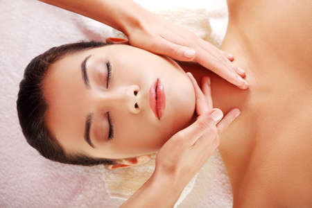 Beautiful young relaxed woman enjoy receiving face massage at spa saloon  photo
