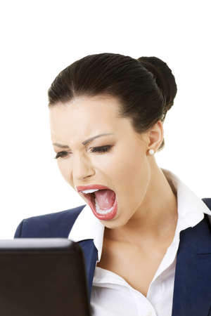 Angry businesswoman shouting on her laptop, isolated on white photo