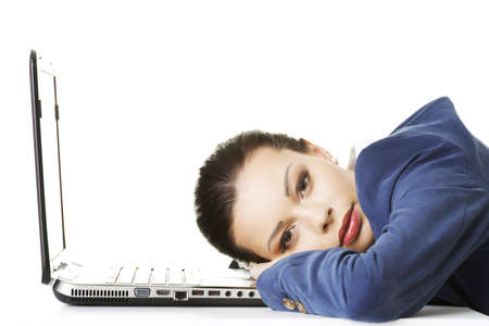 unmotivated: Beautiful bored and tired businesswoman lying down on desk next her laptop