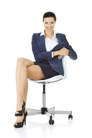 swivel: Beautiful successful businesswoman sitting on ofice chair and smiling, isolated on white