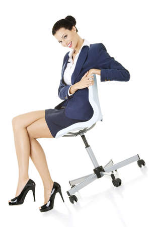 Beautiful successful businesswoman sitting on ofice chair and smiling, isolated on white photo