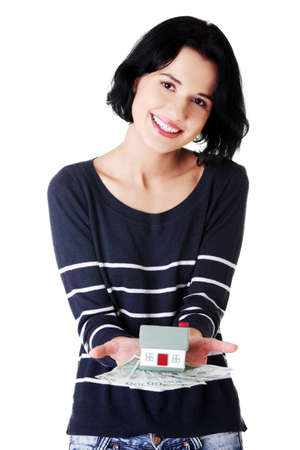 Happy woman holding polish zloty bills and house model over white - real estate loan concept  photo