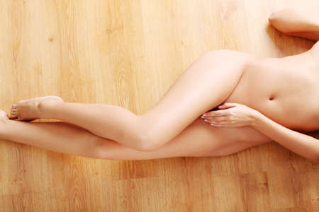 tanned body: Sexy nude woman body (legs) on wooden flor