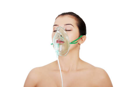 gas mask: Diseased female patient wearing a oxygen mask against white background
