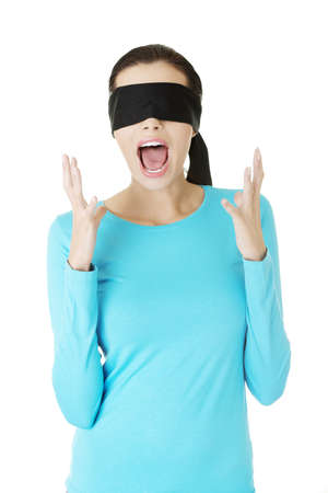 disoriented: Portrait of a beautiful frighten young blindfold woman screaming in panic