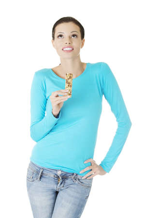 Young woman eating Cereal candy bar, isolated on white photo