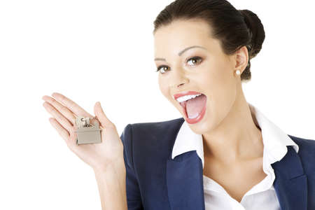 service broker: Portrait of a happy attractive caucasian businesswoman, real estate agent, holding a house key against a white background