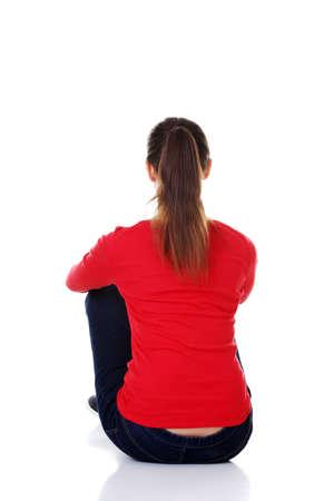 Achter mening van mooie jonge vrouw zittend op de vloer en kijkt in de verte. Geïsoleerd op witte achtergrond. Stockfoto