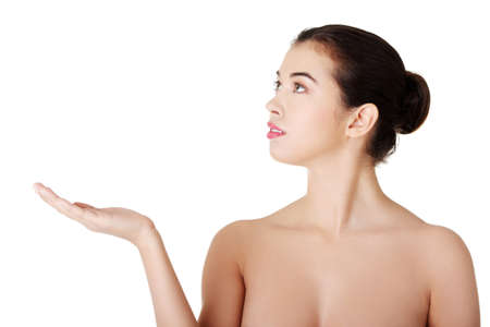 Attractive woman with clean fresh skin presenting copy space on her palm  Stock Photo - 18185534