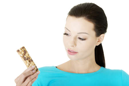 granola: Young woman eating Cereal candy bar, isolated on white  Stock Photo