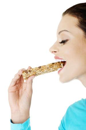 barra de cereal: Mujer joven comer barra de chocolate Cereal, aislado en blanco