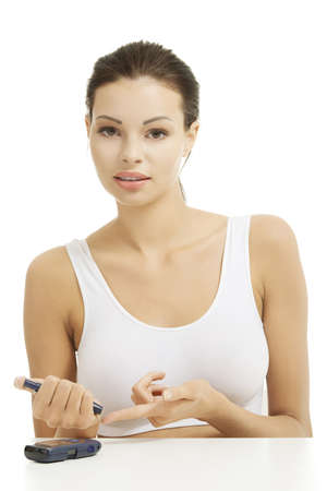 poking: Diabetes patient measuring glucose level blood test using ultra mini glucometer and small drop of blood from finger isolated on a white background