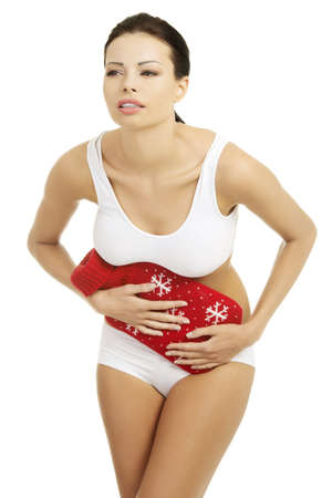 Woman with belly pain holding hot water bottle photo