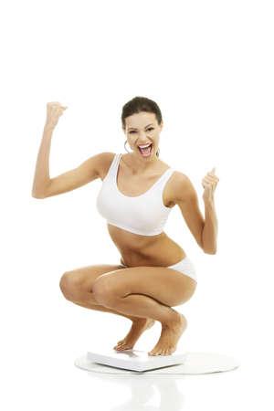 저울에 행복 한 여자. 체중 감량의 개념.