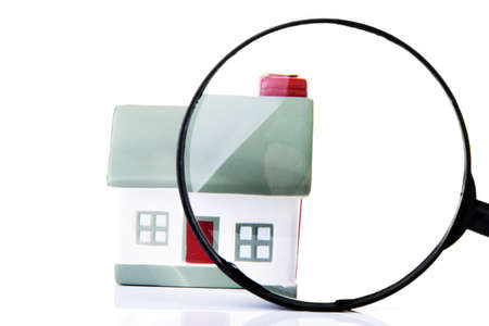optical equipment: Magnifying glass inspecting a model single home building structure. Isolated on white. Real estate search concept.