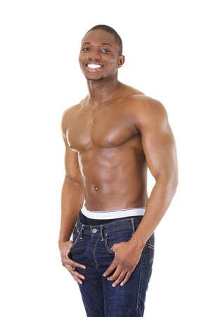 hombres musculosos: Feliz el hombre negro musculoso bien construido en pantalones vaqueros, aislados en blanco Foto de archivo