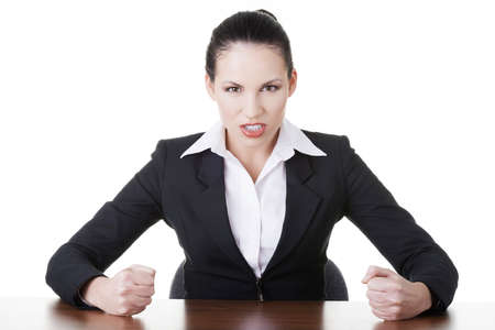 Angry businesswoman at the desk, isolated on white background photo