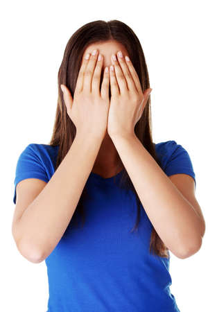 Young teen woman covering her face with hands, isolated on white Stock Photo - 18838498
