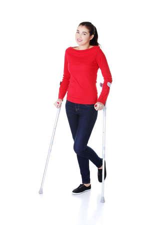 disability insurance: Donna che cammina con le stampelle visto che le varie di infortunio alla gamba