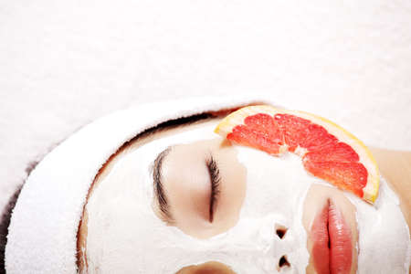 face lift: Attractive young woman with fruit mask on a face at spa saloon  Stock Photo