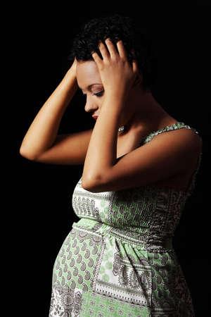 mujer pensativa: La depresi�n y el estr�s de la joven embarazada contra el fondo negro Foto de archivo