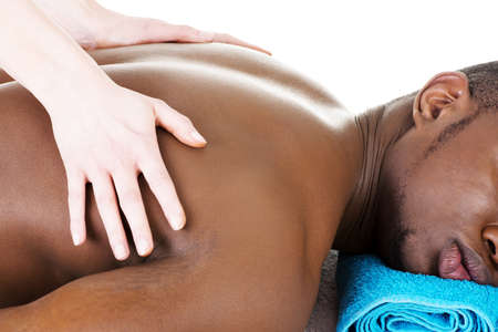Masseur doing massage on man body in the spa salon. photo