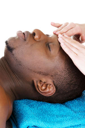 Black man recaiving head massage at spa, isolated on white photo