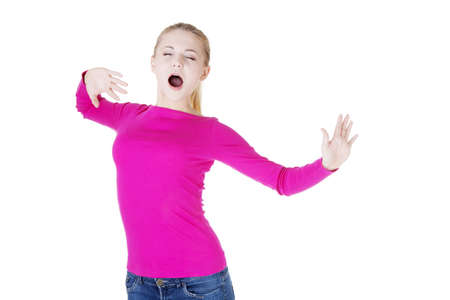 Beautiful blond woman in pink  blouse, yawning and stretching photo