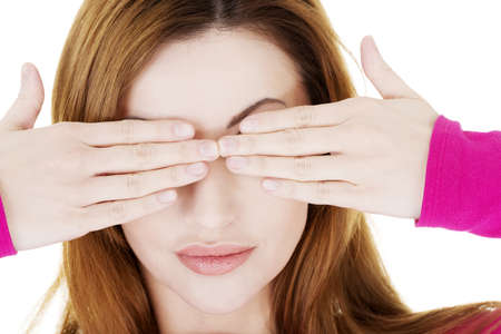 Woman covering eyes with her hands over white background  photo