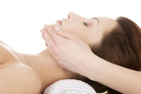 tratamiento facial: Hermosa mujer relajada joven disfruta recibiendo masaje facial en el sal?n de spa