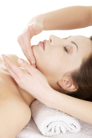 face massage: Beautiful young relaxed woman enjoy receiving face massage at spa saloon