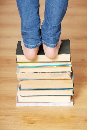 Girl standing on pile of books photo
