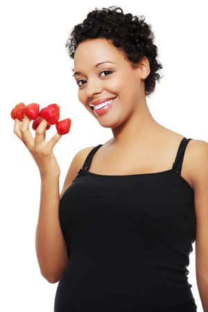 Young happy pregnant afro american woman with strawberries, isolated on white background  photo