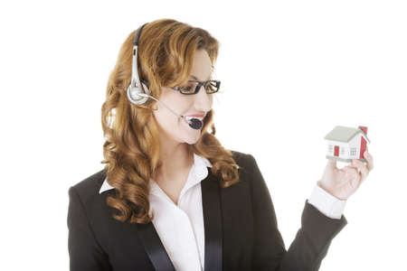 Attractive call center support woman with headset andhouse model in hands. Real estate concept. photo
