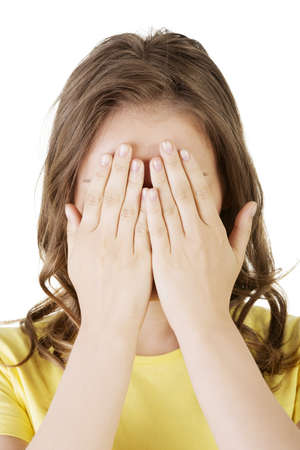 Young teen woman covering her face with hands, isolated on white  Stock Photo - 20085735