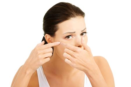 彼女の顔ににきびを持つ若い女性。それを絞るしようとしています。白い背景で隔離されました。
