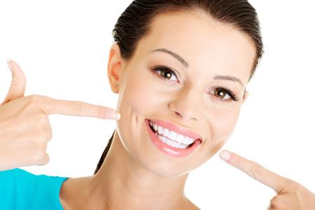 Vrouw toont haar perfecte rechte witte tanden.