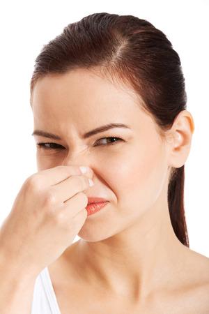 Retrato de una mujer joven con la nariz a causa de un mal olor aislado en blanco Foto de archivo