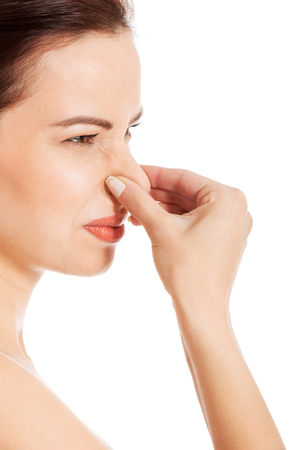Portrait of a young woman holding her nose because of a bad smell  Isolated on white 版權商用圖片 - 24522178
